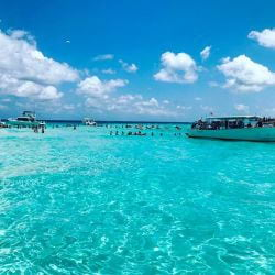 A picture of boat and people standing in the shallow water at Stingray City on Grand Cayman