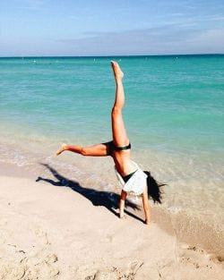 A photo of a girl doing Cartwheels in the sand on Miami Beach.