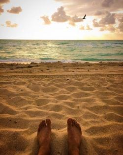 A  picture of two Bare Feet on Miami Beach with ocean in background.