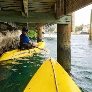 A picture of kayakers taking shelter under a dock to avoid a summer shower in Grand Bahama Bahamas